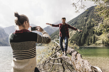 Austria, Tyrol, Alps, woman taking cell phone picture of man balancing on tree trunk at mountain lake - UUF12000