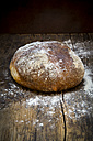 Wheat bread powdered with flour on dark wood - LVF06351