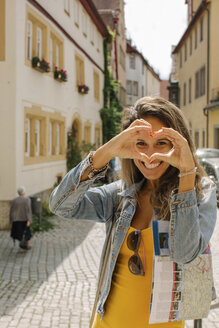 Germany, Rothenburg ob der Tauber, portrait of happy woman shaping heart with her fingers - MOMF00268