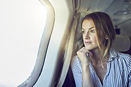 Serious woman looking out of airplane window - PNEF00214