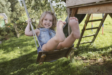 Happy little girl on swing in the garden - KMKF00022