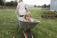 Boy pulling wheelbarrow with his little sister through the garden - KMKF00028