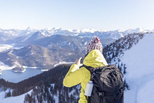 Germany, Bavaria, Alps, hiker with backpack at Lake Walchen taking smartphone picture - MMAF00147