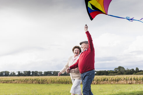 Happy senior couple with kite in rural landscape - UUF12001