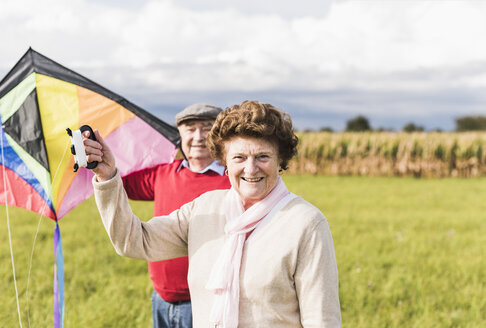 Portrait of smiling senior couple with kite in rural landscape - UUF12004