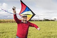 Happy senior man flying kite in rural landscape - UUF12007