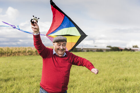 Happy senior man flying kite in rural landscape - UUF12007
