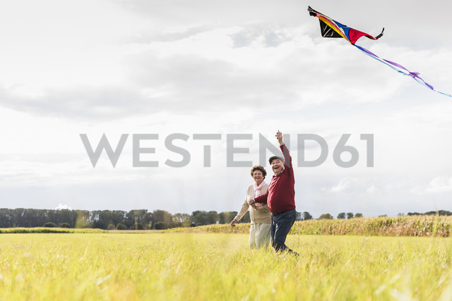 Happy senior couple flying kite in rural landscape - UUF12010