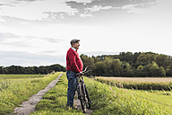 Senior man with bicycle in rural landscape - UUF12013