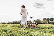 Senior woman pushing bicycle in rural landscape - UUF12022