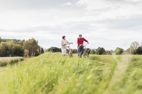 Senior couple pushing bicycles in rural landscape - UUF12025