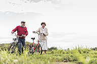 Senior couple pushing bicycles in rural landscape - UUF12028