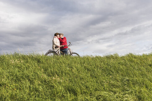 Senior couple with bicycles kissing in rural landscape under cloudy sky - UUF12031