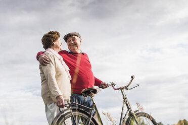 Happy senior couple with bicycles embracing - UUF12034