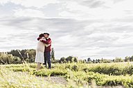 Senior couple hugging in rural landscape - UUF12040
