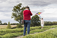 Senior man filming wife flying kite in rural landscape - UUF12043