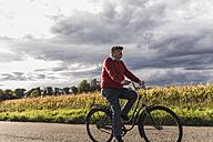 Senior man riding bicycle on country lane - UUF12049