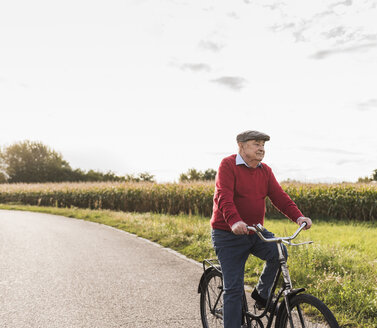 Senior man riding bicycle on country lane - UUF12052