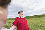 Happy senior man smiling at wife in rural landscape - UUF12055