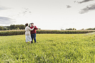 Senior couple dancing in rural landscape - UUF12058