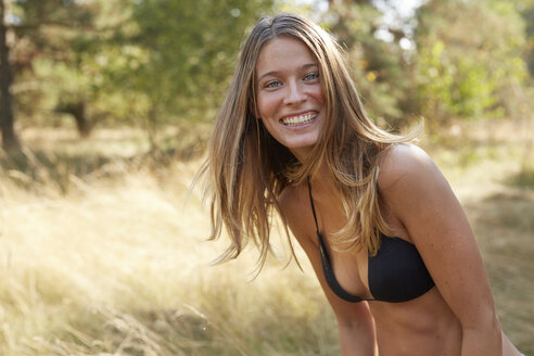 Portrait of laughing young woman wearing bikini top in nature - PNEF00215