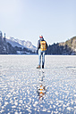 Germany, Berchtesgadener Land, back view of woman with backpack standing on frozen Lake Koenigssee - MMAF00156