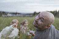 Portrait of father with two children relaxing in meadow - KMKF00038