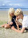 France, Bretagne, Sainte-Anne-la-Palud, La Plage de Treguer, brother and sister examining seashells on the beach - LAF01925