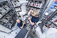 Two colleagues working at industrial robot in modern factory - DIGF02938