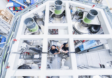 Top view of two colleagues working at industrial robot in modern factory - DIGF02950