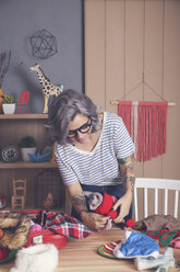 Woman putting pullover on her Sphynx cat at home - RTBF01054