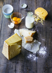 Bottle of milk, pieces of cheese and glass of egg yolks on wood - PPXF00121