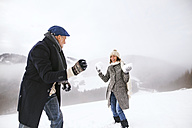 Senior couple having a snowball fight in the snow - HAPF02229