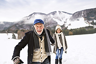 Portrait of senior man walking hand in hand with his wife in snow-covered landscape - HAPF02232