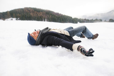 Senior man making a snow angel - HAPF02244