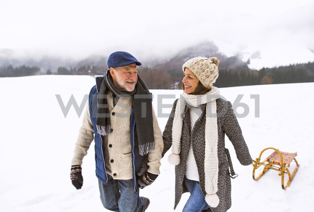 Happy senior couple with sledge walking in snow-covered landscape - HAPF02247