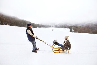 Senior couple having fun with sledge  in snow-covered landscape - HAPF02250