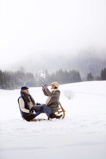 Senior couple with sledge having fun in snow-covered landscape - HAPF02256