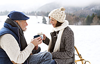 Senior couple having a break with hot beverages in snow-covered winter landscape - HAPF02259