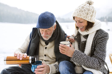 Senior couple having a break with hot beverages in snow-covered winter landscape - HAPF02262