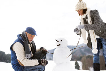 Senior couple building up snowman in winter - HAPF02268