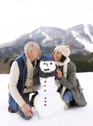 Senior couple with snowman in winter landscape - HAPF02271