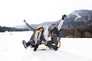 Senior couple posing with snowman on sledge in winter landscape - HAPF02274