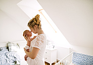 Mother holding crying little baby at home - HAPF02280