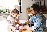 Father playing with little boy sitting on kitchen table - HAPF02283