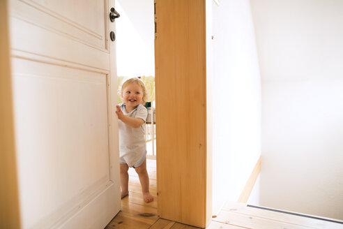 Portrait of happy baby boy opening the door - HAPF02289