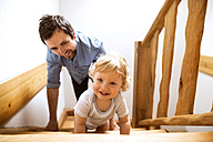 Father with little boy on wooden stairs at home - HAPF02292