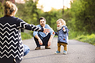 Cute little boy with parents on field path - HAPF02310