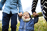 Cute little boy with parents in dandelion field - HAPF02331
