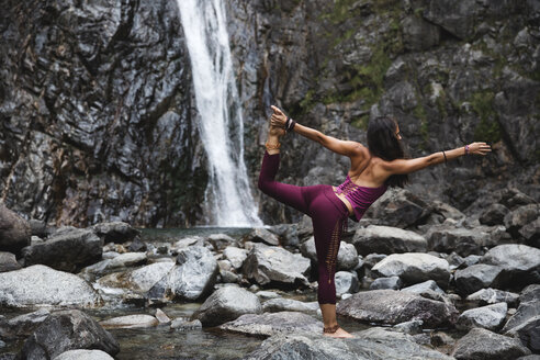 Italy, Lecco, woman doing Lord of the Dance Yoga Pose on a rock near a waterfall - MRAF00252